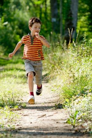 niño corriendo: Chico joven corriendo en la naturaleza Foto de archivo