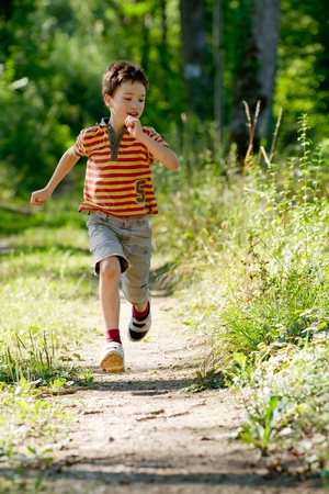 environment protection: Young boy running in nature Stock Photo