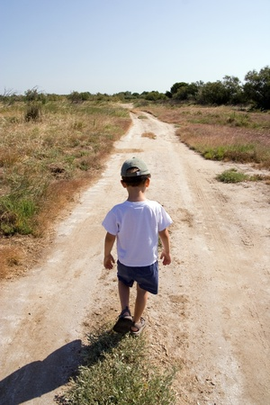 A young child walking on the road photo
