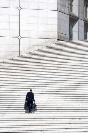 la defense: A businessman climbing white stairs - success concept