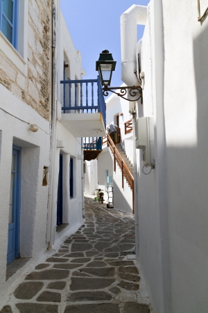 narrow: Classical narrow street with a painted sidewalk in Parikia Stock Photo