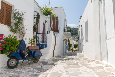 Classical narrow street with a painted sidewalk in Parikia Stock Photo