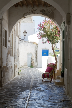 narrow street: Classical narrow street with a painted sidewalk in Parikia Stock Photo