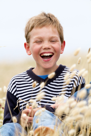 Young blond teenager laughing in the wind - childhood and lifestyle concept photo