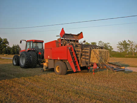 Tractor and hay baler in a field in the evening Imagens