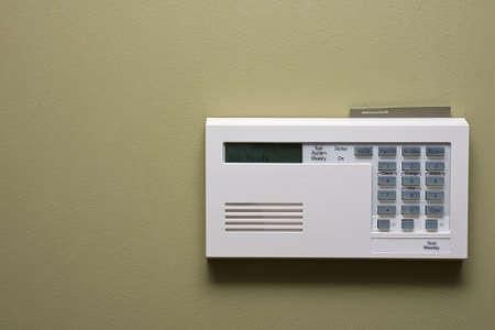 緑の壁にあるホーム セキュリティ コントロール パネル