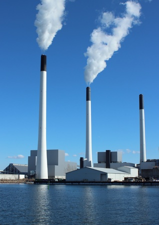 Factory chimneys at energy plant with blue sky and lake photo