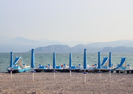 ciclos: Ciclos del agua y sombrillas en la playa vac�a en la ma�ana Foto de archivo