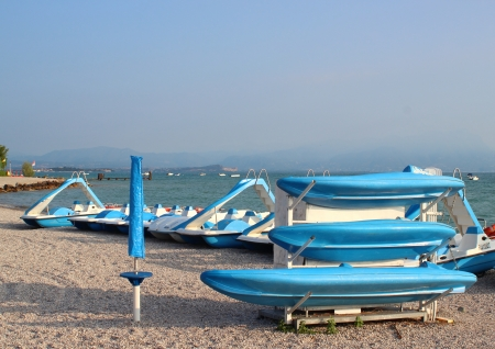 'cycles: Blue boats and water cycles at rubble beach in the morning