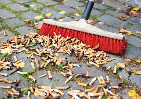 Sweeping a lot of cigarette butts from stone road photo