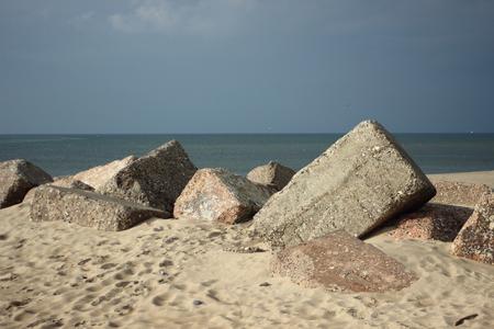 groyne: Large concrete blocks on a beach used for a groyne Stock Photo