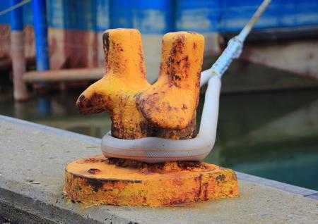 Orange metal pole for mooring of ships at pier photo