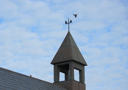 Bell tower of small simple church with cross and birds photo