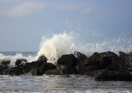 Crashing waves against black rocks at coast photo