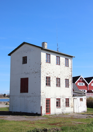 morgage: Isolated abandoned three storage building near new houses Stock Photo