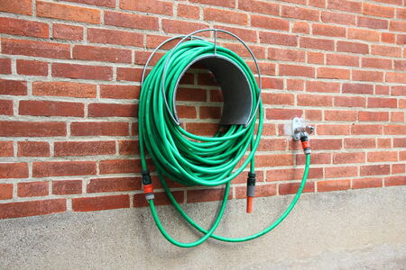 water hose: Green water hose hanging red brick wall Stock Photo
