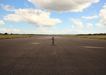 Biking child with helmet on airplane runway photo
