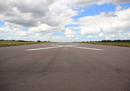 Empty airplane runway with white cross photo