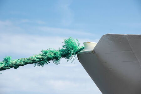 ship bow: Green worn anchor rope on ship bow Stock Photo