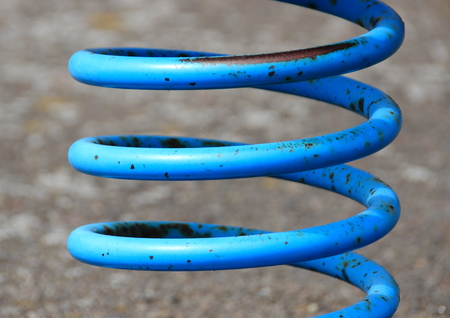 Blue painted metal spring with rust