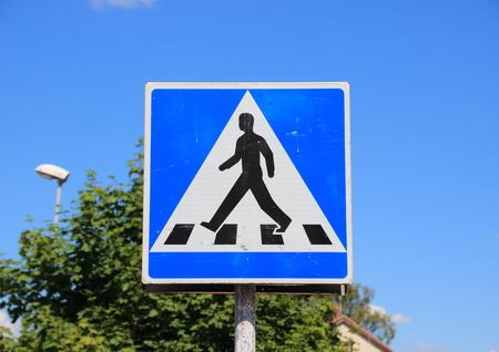 pedestrian sign: Segno pedonale con il cielo blu e l'albero di sfondo