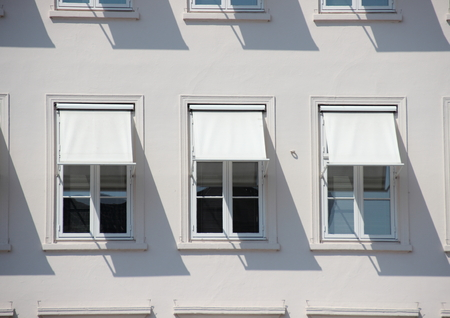 awnings windows: Three windows on grey building with  white awnings and shadow
