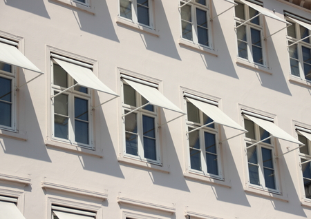awnings windows: Closeup perspective on grey building with  white awning
