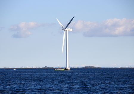 Ocean windmill in rough sea with inspection ship photo