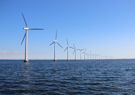 Perspective line of ocean wind mills with dark water and sky Standard-Bild
