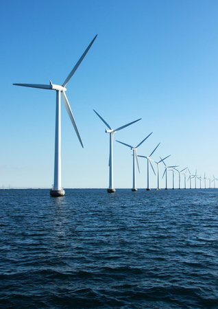 Vertical perspective line of ocean windmills with dark water and sky photo