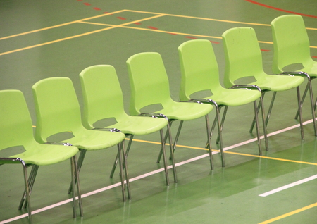 sports hall: Line of green chairs in sports hall