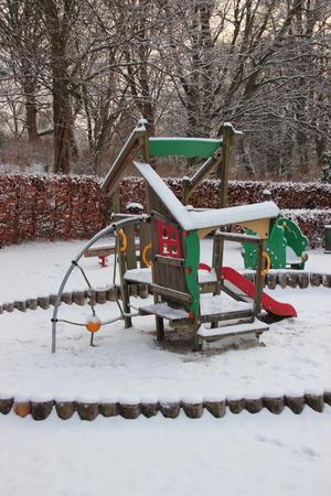 no snow: Public Children Playground  in Winter covered with Snow. No Kids around.