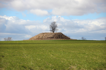 Ancient Burial Mound with Dramatic Clouds and Fresh Green Field Stock Photo