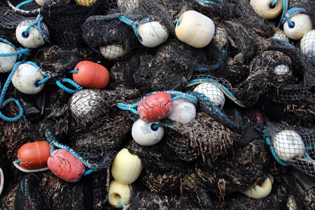 Closeup on Black Fishing Net Pile with Colored Float in Background