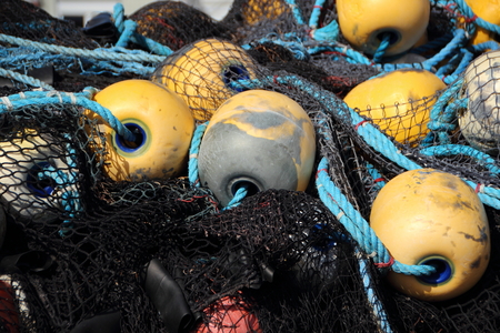 overfishing: Closeup on Black Fishing Net Pile with Yellow Float in Background Stock Photo