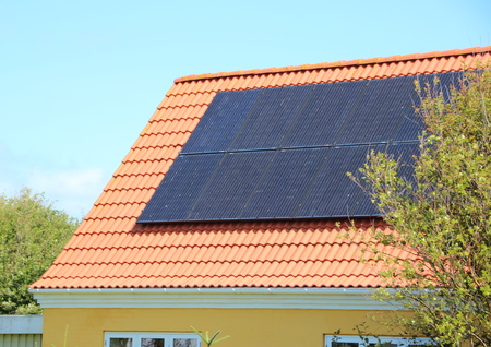solarcell: Solar panel on House Roof with Red Tiles Saving Electricity Stock Photo