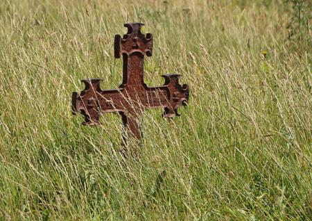 empty tomb: Isolated Rusty Iron Cross at Ancient Graveyard in Grass Field