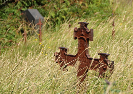 empty tomb: Ancient Graveyard with Single Rusty Iron Cross in Grass field