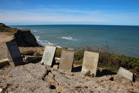 headstone: Ancient Headstone at Edge of Cliff with Erosion Cracks Stock Photo