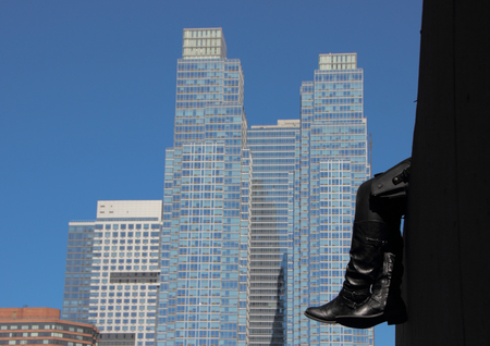 leather boots: Resting Black Leather Boots with Skyscraper Background Abstract Stock Photo