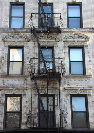 tenement: Fire Escape Steel Ladder on White Apartment Building Facade in New York Stock Photo