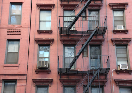 tenement: Fire Escape Steel Ladder on Urban Red Apartment House Facade in New York Stock Photo