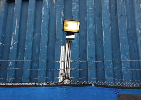 razorwire: Surveillance Search Light on Blue Metal Background with Barbwire