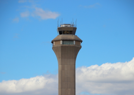control tower: Top of Grey Airport Control Tower with Clouds and Blue Sky