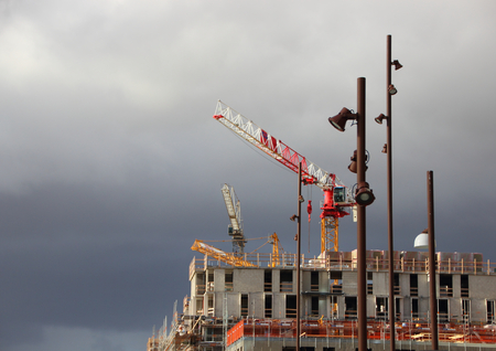 street lamps: Building Site Cranes and Street Lamps with Dark Clouds Stock Photo