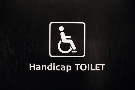 handicap: Isolated White Handicap Disabled Toilet Sign on Black Wood