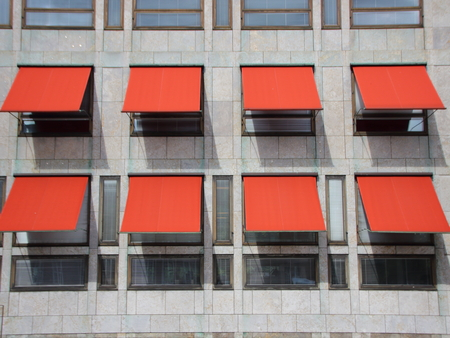 overhang: Red Overhang Sunshade Awning with shadows on Grey Building Facade Protecting from the Sun. Stock Photo