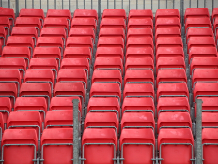 spectator: Closeup on Concert Spectator Steel Platform with Rows of Red Plastic Seats