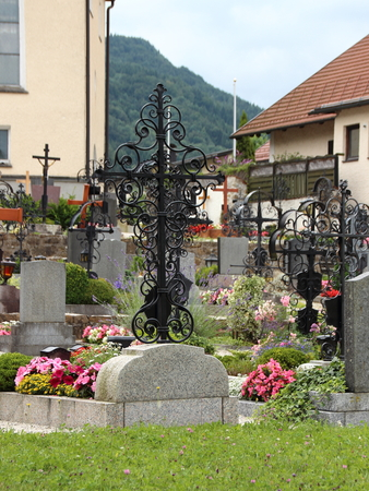 final thoughts: Catholic Graveyard in Austria Europe with Closeup on Handcrafted Ornamented Iron Headstone