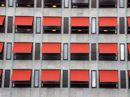 overhang: Twelve Red Overhang Sunshades on Modern Building Facade Protecting from the Sun